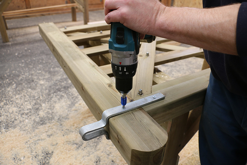Carefully drill two holes for the bolts that attach the gate latch.